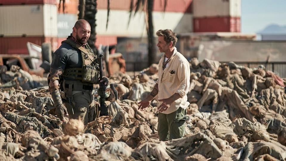 Dave Bautista and Zack Snyder stand among hundreds of zombies in a behind-the-scenes still from Army of the Dead.