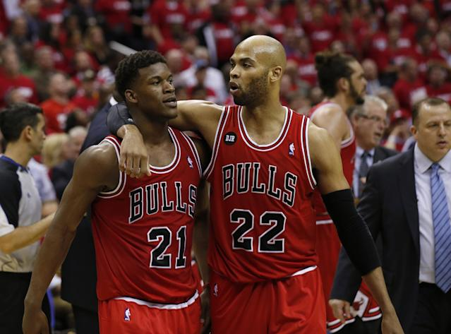 Chicago Bulls guard Jimmy Butler (21) is pulled away by forward Taj Gibson (22) after an altercation with Washington Wizards forward Nene (42), from Brazil, in the second half of Game 3 of an opening-round NBA basketball playoff series on Friday, April 25, 2014, in Washington. Nene received a double technical and was ejected. The Bulls won 100-97. (AP Photo/Alex Brandon)
