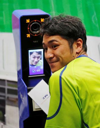 NEC Green Rockets' rugby player Teruya Goto poses with the face recognition system for Tokyo 2020 Olympics and Paralympics, which is developed by NEC corp, during its demonstration in Tokyo, Japan August 7, 2018. REUTERS/Toru Hanai