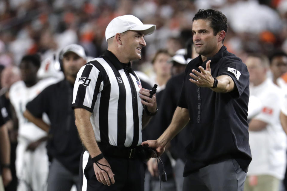 Miami coach Manny Diaz, right, talks with an official during the second half of the team's NCAA college football game against Virginia, Friday, Oct. 11, 2019, in Miami Gardens, Fla. Miami won 17-9. (AP Photo/Lynne Sladky)