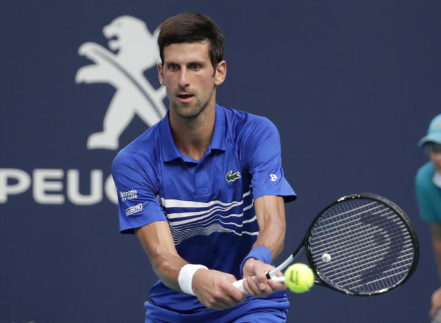 Novak Djokovic, of Serbia, returns to Roberto Bautista Agut, of Spain, during the Miami Open tennis tournament, Tuesday, March 26, 2019, in Miami Gardens, Fla. John (AP Photo/Lynne Sladky)