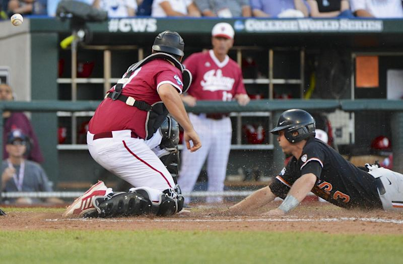 Oregon State's Kavin Keyes, right, scores at home plate as the ball gets away from Indiana catcher Kyle Schwarber, on a sacrifice fly by Jake Rodriguez in the fourth inning of an NCAA College World Series elimination baseball game in Omaha, Neb., Wednesday, June 19, 2013. (AP Photo/Ted Kirk)