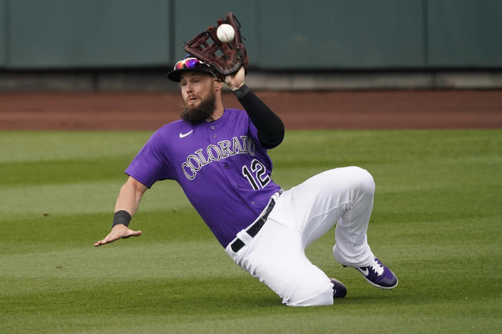 Colorado Rockies' Chris Owings catches a fly out hit by Seattle Mariners' Julio Rodríguez during the second inning of a spring training baseball game, Saturday, March 13, 2021, in Scottsdale, Ariz. (AP Photo/Matt York)