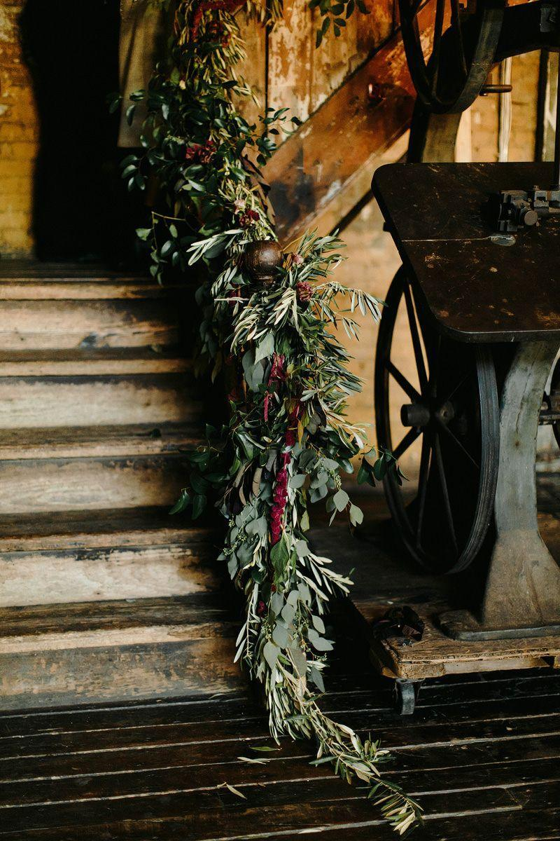 """<p>Rather than cover every railing and table with floor to ceiling flowers, skip the blooms altogether and go green. Draped willow, eucalyptus, redwood, and spruce make for elegant decoration that feels inherently holiday, plus they'll leave behind a fresh scent. Garlands of greenery work on stairwells (as shown here), on fireplace mantles, or down each table at the reception, filled in as needed with moody objet and winter fruits and berries. </p><p><em>Pictured: Planning by <a href=""""http://www.jovemeyerevents.com/"""" rel=""""nofollow noopener"""" target=""""_blank"""" data-ylk=""""slk:Jove Meyer Events"""" class=""""link rapid-noclick-resp"""">Jove Meyer Events</a>.</em></p>"""