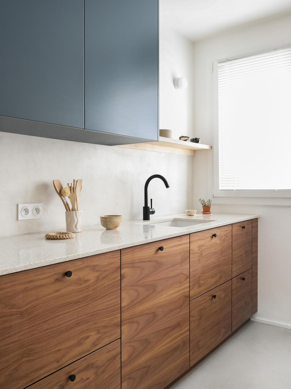 """<div class=""""caption""""><strong>AFTER:</strong> In the peacock blue and walnut kitchen, some pieces are by IKEA, and the cabinet doors are by <a href=""""https://www.helsingo.com/en/"""" rel=""""nofollow noopener"""" target=""""_blank"""" data-ylk=""""slk:Helsingö."""" class=""""link rapid-noclick-resp"""">Helsingö.</a></div>"""