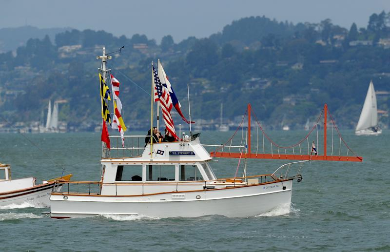 With a sculpture of the Golden Gate Bridge adorning her foredeck, the W.L. Stewart III rides in a boat parade celebrating the Golden Gate Bridge's 75th anniversary on Sunday, May 27, 2012, in San Francisco. The commemoration included a vintage car show, an exhibit of roughly 1,558 pairs of shoes representing people who have committed suicide by jumping from the span, and a fireworks display slated for evening. (AP Photo/Noah Berger)