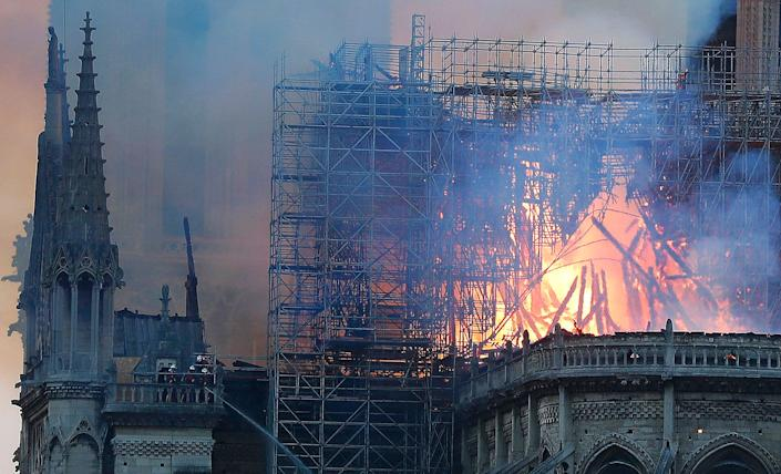 Firefighters tackle the blaze as flames and smoke rise from Notre Dame cathedral as it burns in Paris, April 15, 2019. (Photo: Thibault Camus/AP)