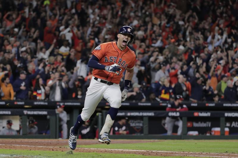 FILE - In this Oct. 30, 2019, file photo, Houston Astros' Carlos Correa reacts to his RBI single during the fifth inning of Game 7 of the baseball World Series against the Washington Nationals in Houston. The last time these teams played the Nationals were celebrating their World Series title in Houston. Since then the Astros have become the league's villains, with a sign-stealing scandal tarnishing their reputation and casting a shadow on their 2017 title. (AP Photo/David J. Phillip, File)