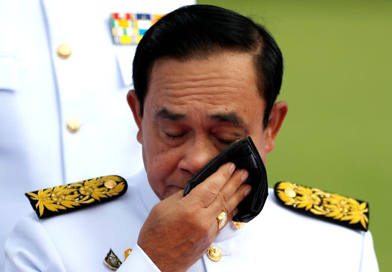 FILE PHOTO: Thailand's Prime Minister Prayuth Chan-ocha wipes his face during a family photo session with new cabinet ministers at the Government House in Bangkok