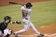 Milwaukee Brewers' Adrian Houser (37) hits a solo home run during the fourth inning of a baseball game against the Miami Marlins, Saturday, May 8, 2021, in Miami. At left is Miami Marlins catcher Chad Wallach. (AP Photo/Lynne Sladky)