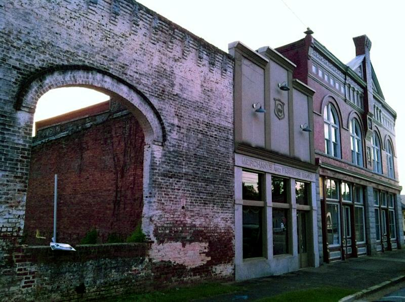 """This Oct. 1, 2013 photo shows the archways and brick wall of an old building in Grantville, Ga., that is used to film a scene in the AMC TV drama """"The Walking Dead."""" Tourists come to the west Georgia town to see the wall and other nearby buildings where scenes from the show were filmed. (AP Photo/Jeff Martin)"""