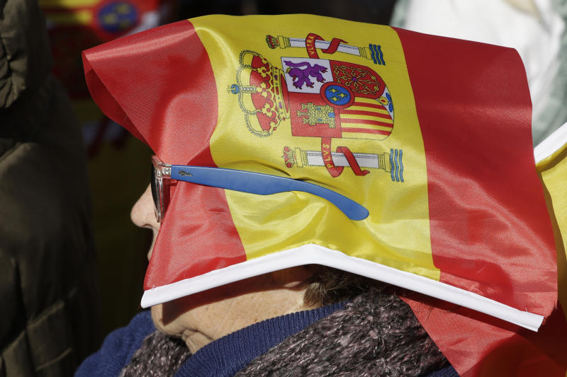 A woman with a Spanish flag covering her head listens to speeches in a rally to promote 'Spanish Unity' during a rally by the right wing VOX party in Madrid, Spain, Saturday, Oct. 26, 2019. The VOX rally comes 2 days after the exhumation and reburial of Spanish dictator Gen. Francisco Franco from the grandiose Valley of the Fallen mausoleum outside Madrid to their new resting place at the Mingorrubio cemetery, 57 kilometers (35 miles) away. (AP Photo/Paul White)