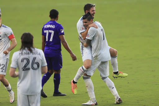New England Revolution midfielder Kelyn Rowe (11) celebrates with forward Gustavo Bou (7) after an MLS playoff soccer match against Orlando City, Sunday, Nov. 29, 2020, in Orlando, Fla. (AP Photo/Matt Stamey)
