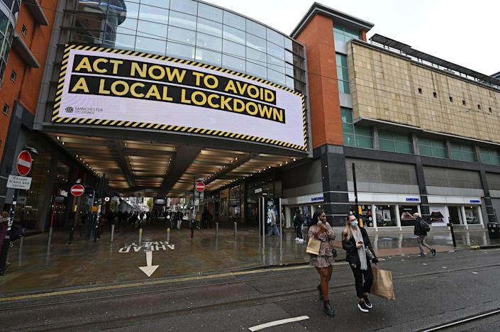 Shoppers wearing face coverings pass beneath an electronic sign reminding pedestrians to 'act now to avoid a local lockdown' outside the Arndale Centre in Manchester. (Getty)