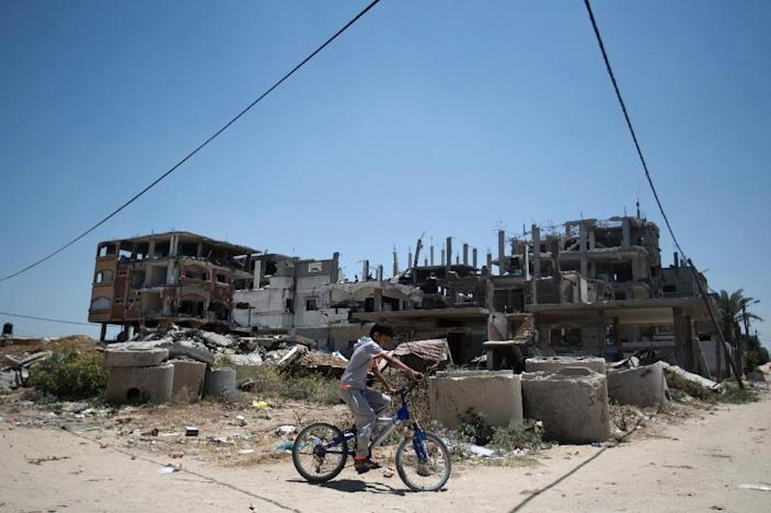 A Palestinian boy rides his bicycle July 3, 2015, past the rubble of buildings destroyed during the 50-day war between Israel and Hamas' militants in the summer of 2014 in the Beit Hanun, northern Gaza Strip (AFP Photo/Mohammed Abed)