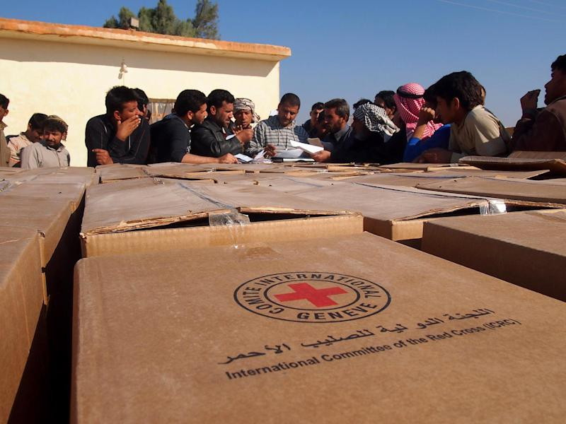 This image provided by the International Committee of the Red Cross (ICRC) on Wednesday, Jan. 15, 2014 shows ICRC staff preparing for a distribution of food and essential items that each family displaced by violence in Fallujah will receive, in Al-Rahhaliyah, south of Ramadi, Iraq. International aid agencies warned Wednesday, Jan. 15, 2014 that the continuing violence in Iraq's western province of Anbar would bring more hardships to the locals and displaced people, as the country's premier declared that the weeks-long standoff between security forces and the militants could take long time.(AP Photo/Majda Flihi, ICRC)