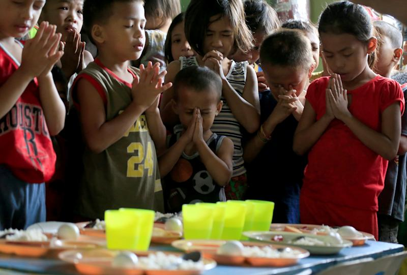 Children pray before eating their free meals inside a missionary house during a feeding program funded by a South Korean missionary, at a slum area in Baseco, Tondo city, metro Manila, Philippines January 2, 2018. REUTERS/Romeo Ranoco