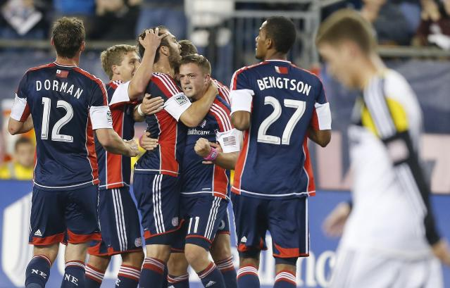 New England Revolution's Andy Dorman (12), Kelyn Rowe (11), Jerry Bengtson (27) and teammates celebrate a goal by A.J. Soares, center, as Columbus Crew's Chad Barson, right, walks past in the first half of an MLS soccer game in Foxborough, Mass., Saturday, Oct. 19, 2013. (AP Photo/Michael Dwyer)