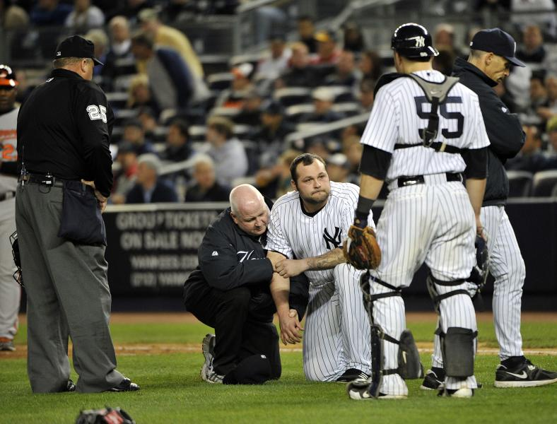 Trainers help New York Yankees relief pitcher Joba Chamberlain, third from right, reactsafter he was hit by a broken bat when Baltimore Orioles' Matt Wieters hit a single during the twelfth inning of Game 4 of the American League division baseball series on Thursday, Oct. 11, 2012, in New York. (AP Photo/Bill Kostroun)