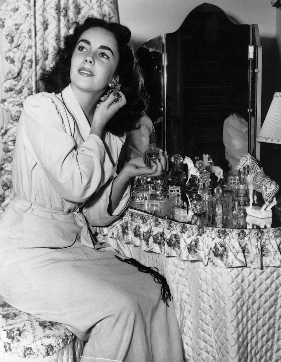 <p>Elizabeth gives fans a glimpse at how she achieves her movie star look as she poses at her vanity in 1948. </p>