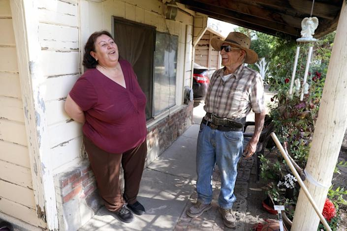 Jovita Torres with her friend and neighbor, Rodolfo Romero, outside a house.