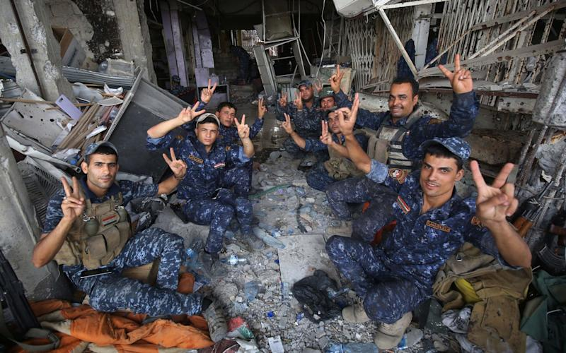Members of the Iraqi federal police flash the sign for victory in celebration in the Old City of Mosul on July 8, 2017 - Credit: AFP