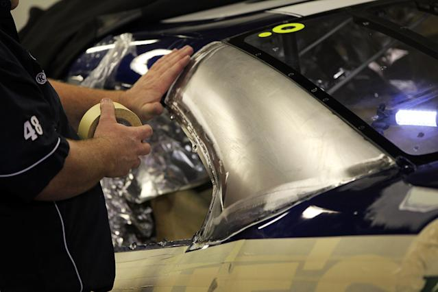 DAYTONA BEACH, FL - FEBRUARY 17: A crew member works on the C-post of the #48 Lowe's Chevrolet of Jimmie Johnson after NASCAR confiscated the old one due to a modification violation in an initial inspection at Daytona International Speedway on February 17, 2012 in Daytona Beach, Florida. (Photo by Jamie Squire/Getty Images)