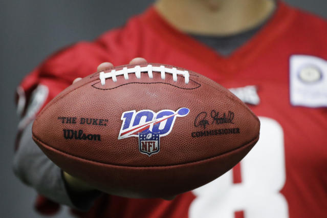 In this Oct. 17, 2019, photo, Philadelphia Eagles practice squad quarterback Kyle Lauletta displays a football during an interview with The Associated Press at the NFL football team's training facility in Philadelphia. Those shiny NFL 100 logos on all the footballs being used to commemorate the leagues centennial season are part of a lengthy process that goes into making each handcrafted leather game ball. Wilson has been the official game ball of the NFL since 1941. The size, shape and feel of the football have evolved over the years, but the personal touch remains the same.(AP Photo/Matt Rourke)