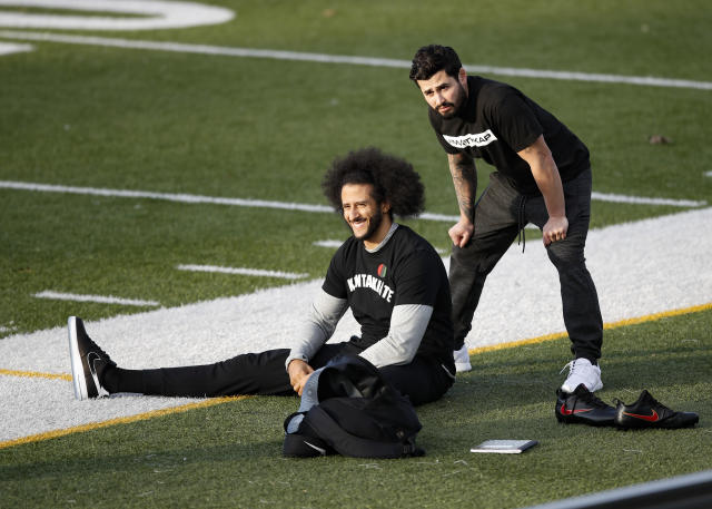 Free agent quarterback Colin Kaepernick, left, stretches before a workout for NFL football scouts and media, Saturday, Nov. 16, 2019, in Riverdale, Ga. (AP Photo/Todd Kirkland)