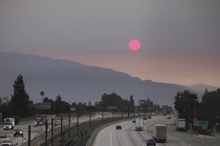 "Smoke from wildfires burning east of Los Angeles dims the sunrise, as seen from Pasadena. <span class=""copyright"">(John Antczak / Associated Press)</span>"