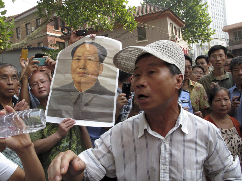 Supporters of former politician Bo Xilai gather near a poster of former Chinese leader Mao Zedong outside the Jinan Intermediate People's Court in Jinan in eastern China's Shandong province on Thursday, Aug. 22, 2013. Ousted populist Chinese politician Bo Xilai went on trial Thursday on charges of bribery, embezzlement and abuse of power, marking the ruling Communist Party's attempts to draw a line under one of its most lurid political scandals in decades. (AP Photo/Gillian Wong)