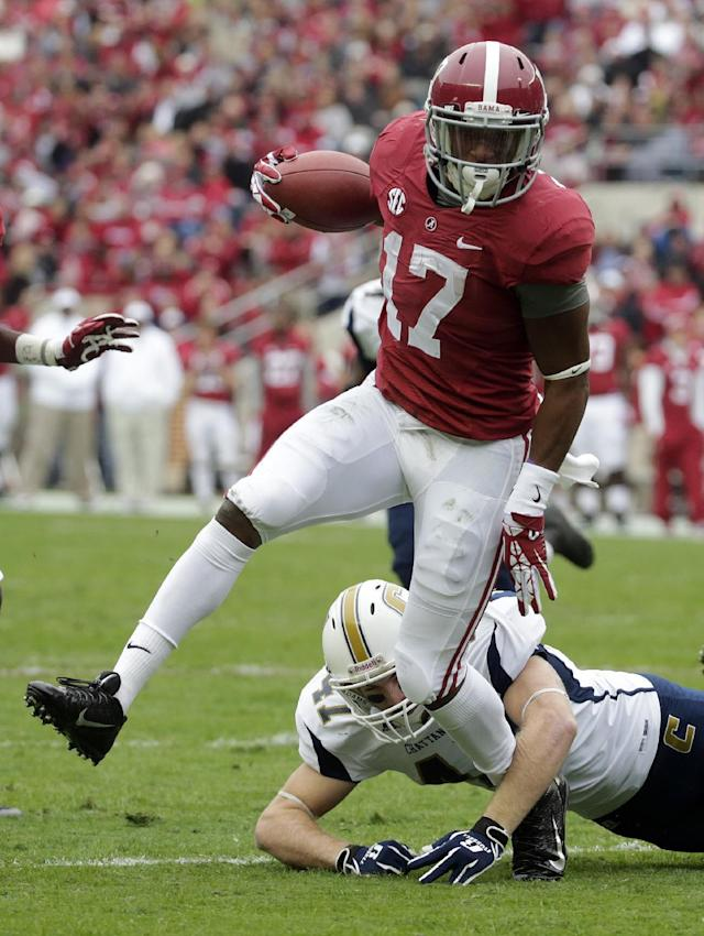 Alabama running back Kenyan Drake (17) scores a touchdown as Chattanooga defensive back Zach McCarter (47) defends during the first half of an NCAA college football game in Tuscaloosa, Ala., Saturday, Nov. 23, 2013. (AP Photo/Dave Martin)
