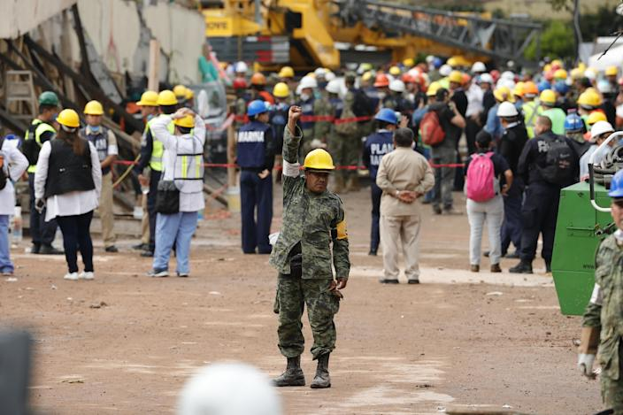 <p>A member of the Mexican Army raises his hand asking for absolute silence as rescue services and volunteers search for victims under the debris of the school that collapsed in Mexico City, Mexico, Sept. 21, 2017. (Photo: Jose Mendez/EPA-EFE/REX/Shutterstock) </p>