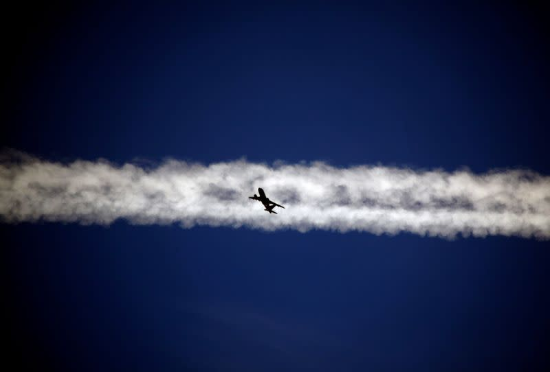 FILE PHOTO: FILE PHOTO: An aeroplane flies beneath the jet stream of another above the Italian city of Padova