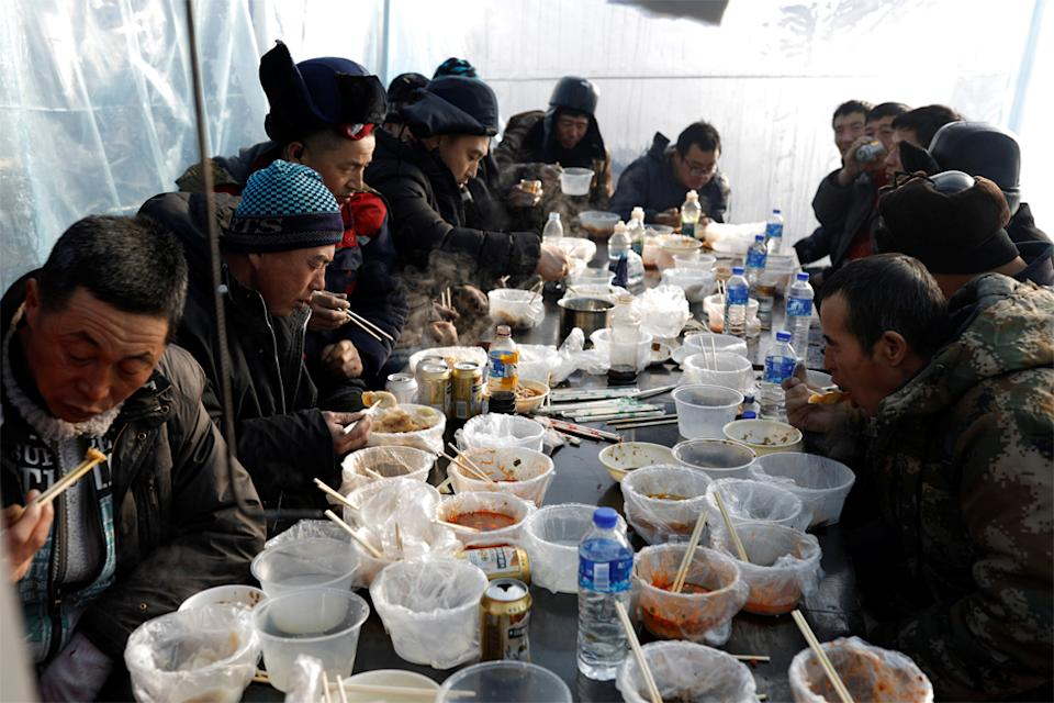 Workers eat lunch inside a makeshift canteen