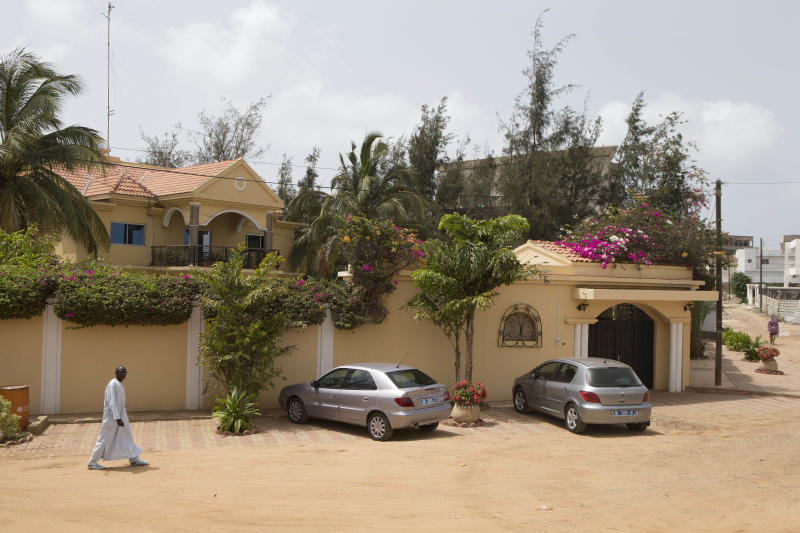 In this Friday, July 5, 2013 photo, a man walks past the home where former Chadian dictator Hissen Habre was taken into custody by paramilitary police on June 30, on a quiet backstreet in an upscale neighborhood of Dakar, Senegal. For more than 20 years, Habre lived a life of luxurious exile in Senegal, taking a second wife and watching 'Seinfeld' shows. But 3,000 miles east of here, a truth commission and rights workers in Chad were documenting widespread abuses during Habre's rule, including disappearances, torture and prison cells so cramped that inmates often died for lack of air. On Tuesday, July 2, 2013, judges at a special court in Dakar formally charged Habre with crimes against humanity, war crimes and torture. (AP Photo/Rebecca Blackwell)