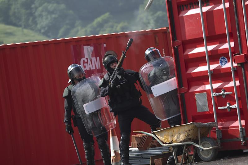 Riot police officers shoot tear gas against miners, unseen, during clashes following a demonstration after blocking a motorway in Campomanes, Oviedo, Spain, Tuesday, June 12, 2012. Strikes, road blockades, and mine sit-ins continue as 8,000 mineworkers at over 40 coal mines in northern Spain continue their protests against government action to cut coal subsidies. (AP Photo/Emilio Morenatti)