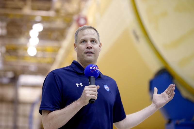 NASA Administrator Jim Bridenstine talks to reporters in front of the core stage of the Space Launch System, which will power the Artemis 1 lunar mission, as he visits the NASA Michaud Assembly Facility in New Orleans, Thursday, Aug. 15, 2019. (AP Photo/Gerald Herbert)
