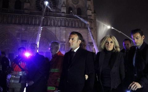 French President Emmanuel Macron (C) and his wife Brigitte Macron pay a visit to firemen fighting against a fire burning the roof of the Notre-Dame cathedral - Credit: Rex