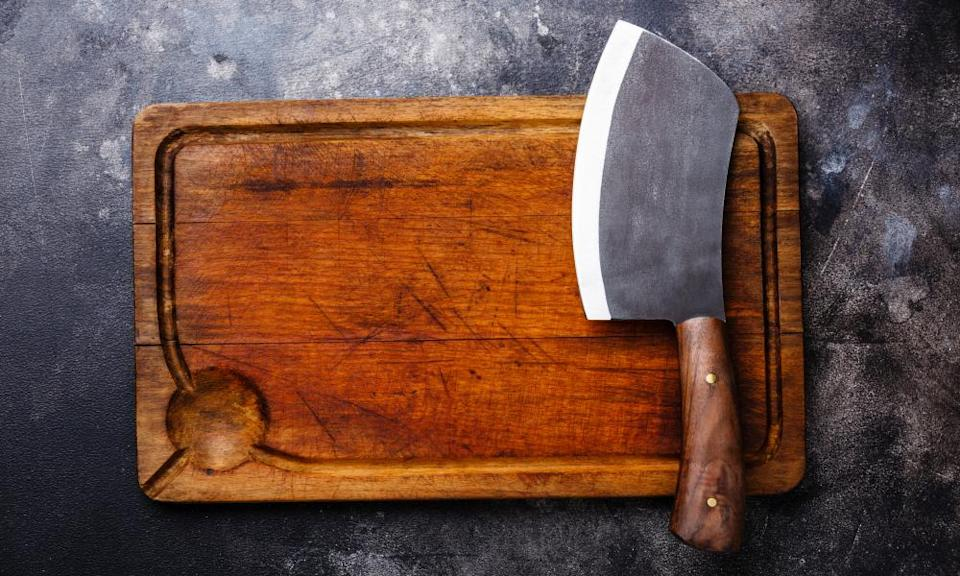 Meat cleaver and empty chopping board against dark grey background