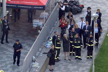 FILE PHOTO: Britain's Prime Minister, Theresa May, speaks to police officers as she visits the scene of a tower block which was destroyed in a fire disaster, in north Kensington, West London, Britain June 15, 2017. REUTERS/Peter Nicholls/File Photo