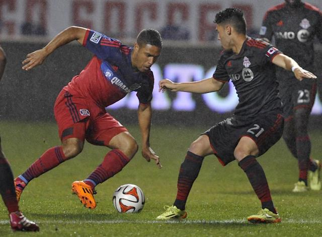 Chicago Fire's Quincy Amarikwa, left, dribbles around Toronto FC's Jonathan Osorio (21) during the second half of an MLS soccer game in Bridgeview, Ill., Wednesday, July 2, 2014. The game ended in a 1-1 tie. (AP Photo/Paul Beaty)