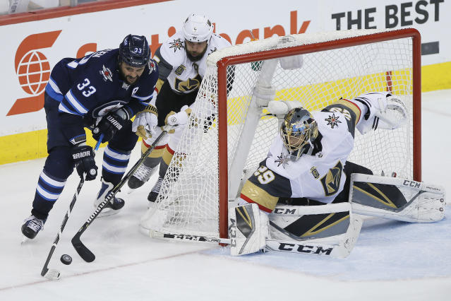 Winnipeg Jets' Dustin Byfuglien (33) attempts the wraparound on Vegas Golden Knights' Deryk Engelland (5) and goaltender Marc-Andre Fleury (29) during the third period of Game 1 of the NHL hockey playoffs Western Conference finals, Saturday, May 12, 2108, in Winnipeg, Manitoba. (John Woods/The Canadian Press via AP)