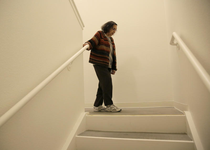 Helen Wagar, who is in her 80s, walks over the spot in a stairway where she fell over another woman who was laying in the dark during the recent power blackouts at the Villas at Hamilton housing complex for low income seniors Wednesday, Oct. 30, 2019, in Novato, Calif. Pacific Gas & Electric officials said they understood the hardships caused by the blackouts but insisted they were necessary. (AP Photo/Eric Risberg)