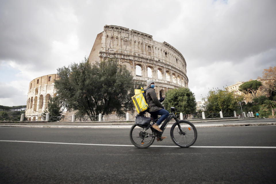 A food delivery worker cycles past the Colosseum, in Rome, Thursday, Dec. 24, 2020. Italy went into a modified nationwide lockdown Thursday for the Christmas and New Year period, with restrictions on personal movement and commercial activity similar to the 10 weeks of hard lockdown Italy imposed from March to May when the country became the epicenter of the outbreak in Europe. (Cecilia Fabiano/LaPresse via AP)