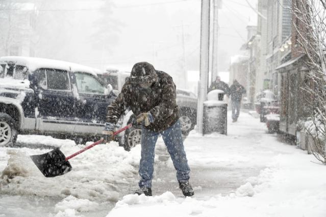 <p>Wayne Cooper shovels slush off of Main Street in West Stockbridge, Mass., to keep water draining, Wednesday, March 2, 2018. (Photo: Ben Garver/The Berkshire Eagle via AP) </p>