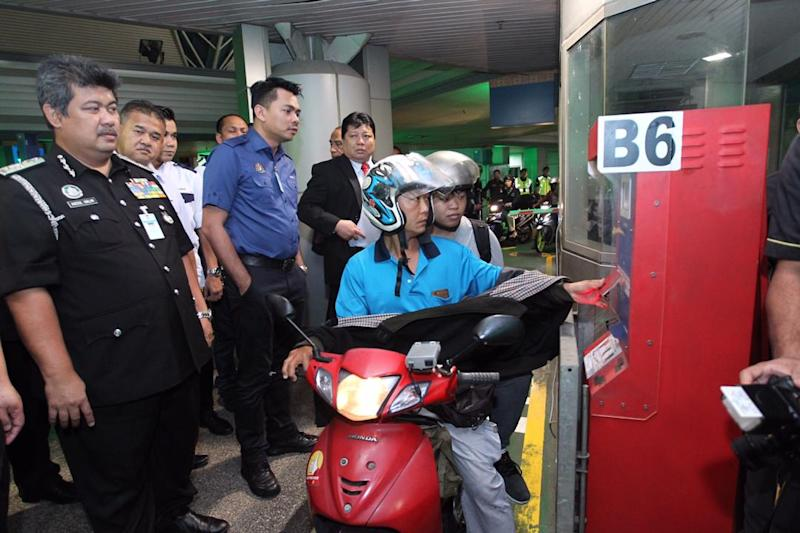 Deputy Home Minister Datuk Azis Jamman (second left) watches a motorcycle rider using his RFID card at the CIQ Complex at the Sultan Iskandar Building in Johor Baru February 11, 2019.— Picture courtesy of the Johor Immigration Department