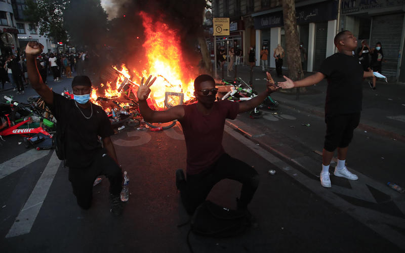 Protesters kneel and react by a burning barricade during a demonstration Tuesday, June 2, 2020 in Paris. Paris riot officers fired tear gas as scattered protesters threw projectiles and set fires at an unauthorized demonstration against police violence and racial injustice. Several thousand people rallied peacefully for two hours around the main Paris courthouse in homage to George Floyd and to Adama Traore, a French black man who died in police custody. (AP Photo/Michel Euler)