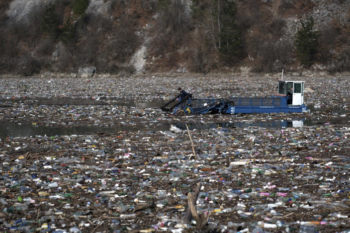 A machine collects garbage floating in the Drina river near Visegrad, eastern Bosnia, Wednesday, Feb. 24, 2021. Environmental activists in Bosnia are warning that tons of garbage floating down the Balkan country's rivers are endangering the local ecosystem and people's health. The Drina River has been covered for weeks with trash that has piled up faster than the authorities can clear it out. (AP Photo/Kemal Softic)