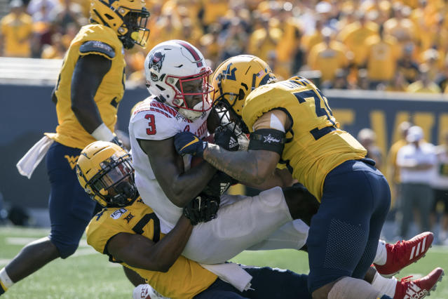 North Carolina State wide receiver Emeka Emezie (3) is tackled by West Virginia cornerback Hakeem Bailey (24) and linebacker Josh Chandler (35) during the second half of an NCAA college football game Saturday, Sept. 14, 2019, in Morgantown, W.Va. (AP Photo/Raymond Thompson)
